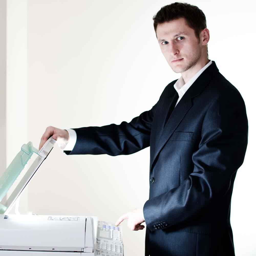 Man standing at multi function printer